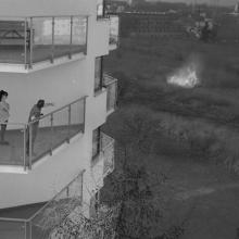 Gráf Dóra: Távolság A szerencse pillanatai – tetszőleges eszközzel A kép egy nem mindennapi pillanatot ábrázol. A tűzeset időben történő felfedezése szerencsés eseménynek mondható. A két alak és a veszélyforrás közti távolság áthidalhatatlannak tűnik. Biztos távolból, a magasból szemlélve figyelik a pusztító lángokat, amik így inkább érdekességként, izgalmas látványosságként jelennek meg előttük, mintsem a félelem forrásaként. A néző szerepe is problematikus. Kik vagyunk mi és honnan figyeljük az eseményeke